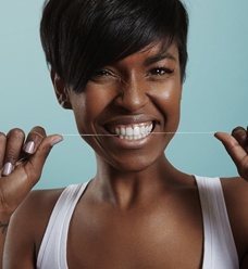 attractive woman flossing her teeth