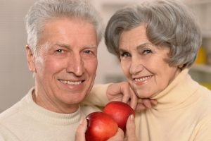 older couple eating apples