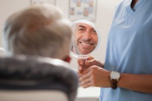dental patient smiling in mirror