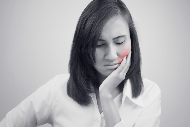 a woman holding her cheek in pain