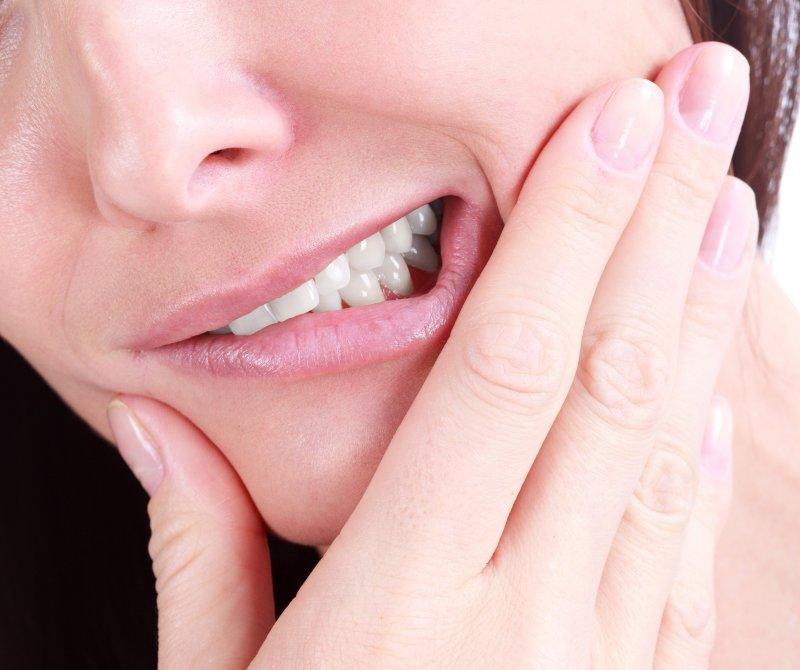 a woman holding her jaw in pain