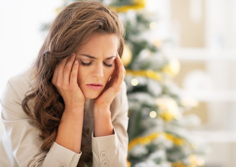 a woman stressed with a Christmas tree in the background
