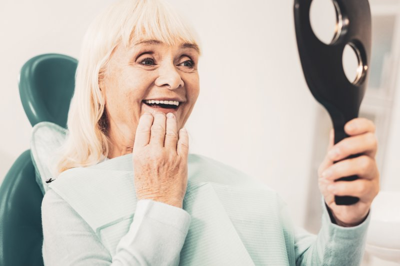an older woman looking at her smile in the mirror