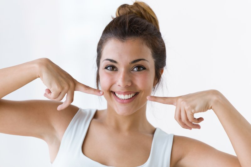 a young woman in a white tank top pointing to her healthy smile