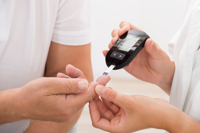 a person having their finger pricked to check their blood sugar levels