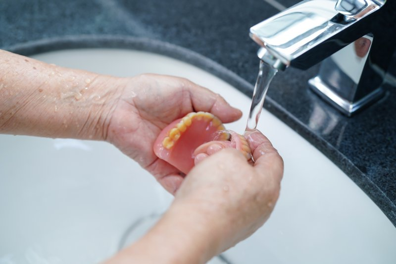 a person cleaning their dentures under a faucet