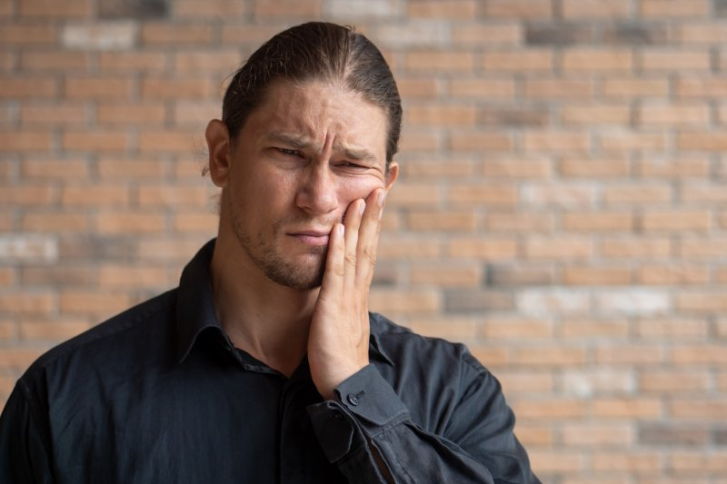 a man wearing a black button-down shirt and holding his cheek in pain because of tooth decay