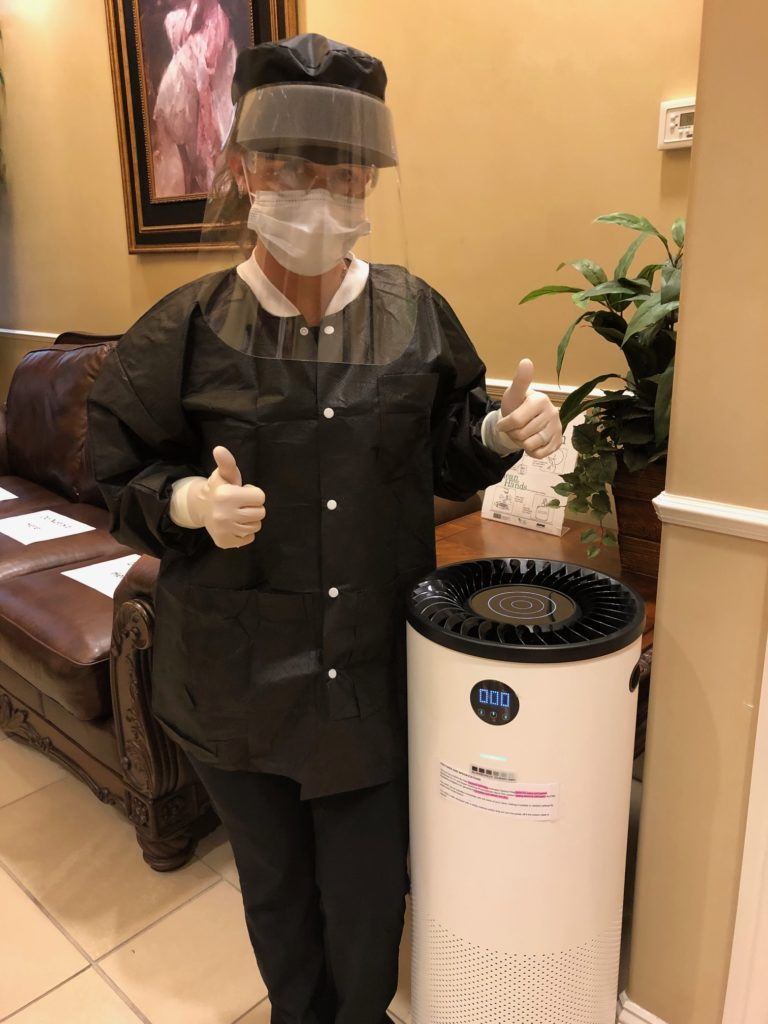 a dental professional giving a thumbs up while standing next to an air purifier