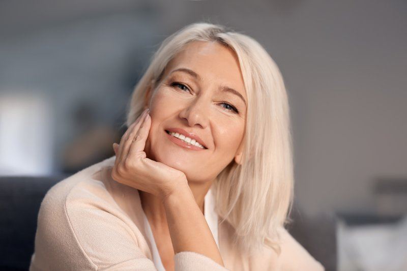 a middle-aged, blonde woman holding her head up with her hand and smiling