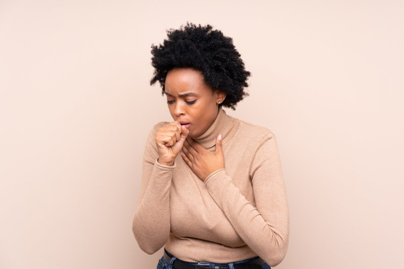 a young woman wearing a cream blouse and coughing into her hand
