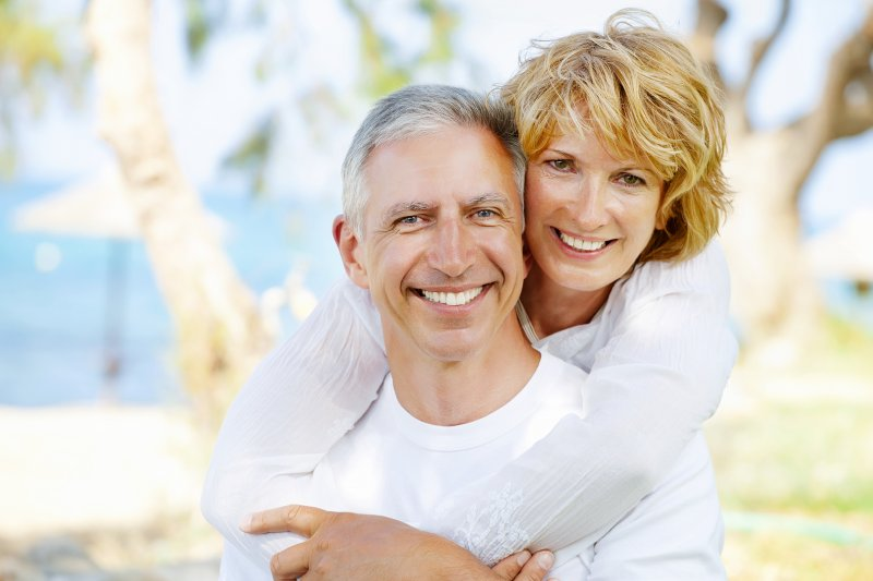 a happy, middle-aged couple hugging and smiling while enjoying the outdoors