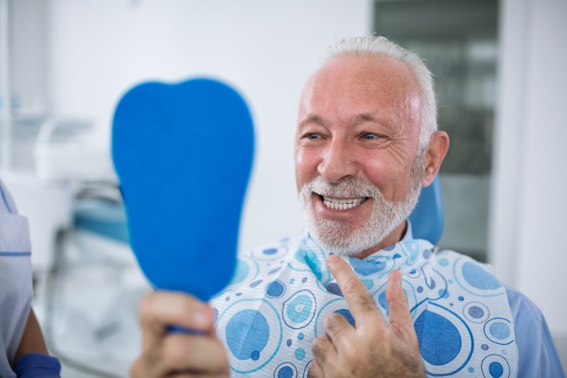 an older man admiring his new smile in the mirror after receiving dental implants