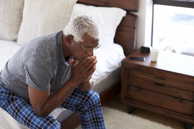 an older man sitting on the side of his bed experience the effects of Alzheimer's disease in Jacksonville