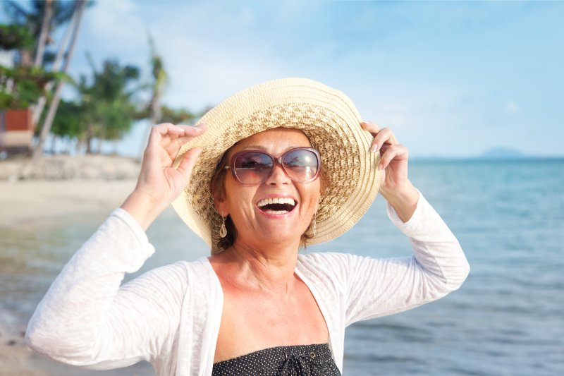 an older woman holding onto her hat while standing in the ocean and smiling after receiving dental implants in Jacksonville