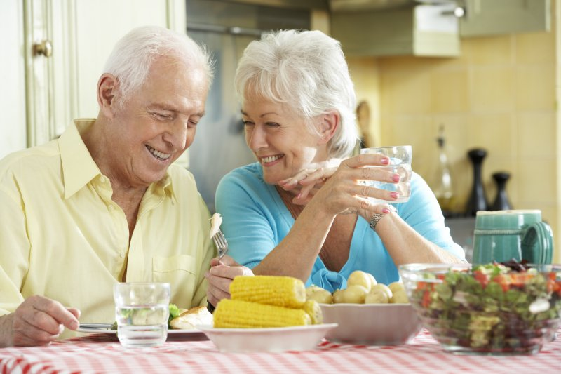 an older couple sitting at a table that is full of delicious summer foods in Jacksonville
